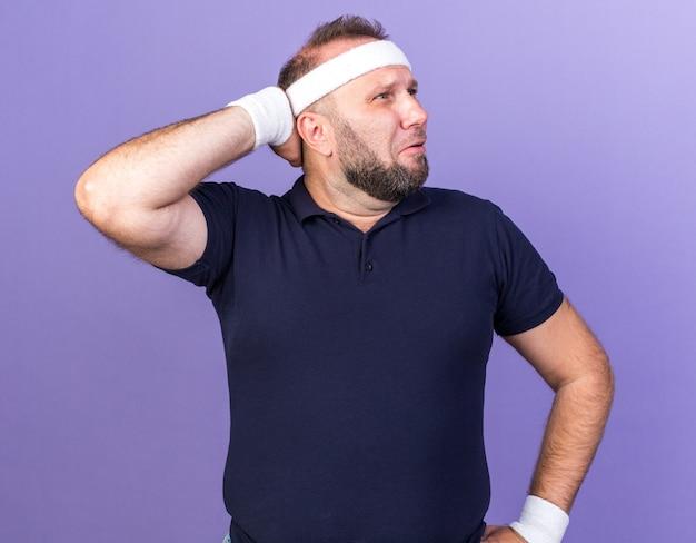 Homem adulto eslavo e triste, esportivo, usando bandana e pulseiras, colocando a mão na cabeça para trás e olhando para o lado isolado na parede roxa com espaço de cópia