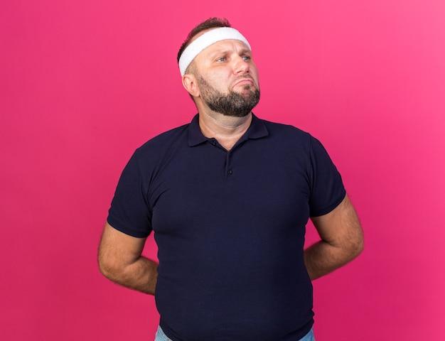 Homem adulto eslavo e triste, esportivo, usando bandana e pulseiras de mãos dadas para trás e olhando para o lado isolado na parede rosa com espaço de cópia