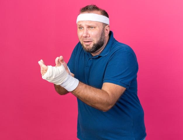 Homem adulto eslavo e triste, esportivo, usando bandana e pulseiras, olhando e apontando para o lado isolado na parede rosa com espaço de cópia