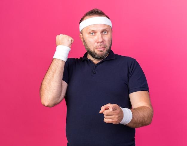 Homem adulto eslavo esportivo sério usando bandana e pulseiras, mantendo o punho erguido e apontando isolado na parede rosa com espaço de cópia