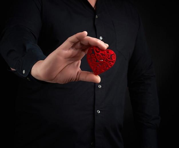 Homem adulto está vestindo uma camisa preta e segurando um coração vermelho esculpido