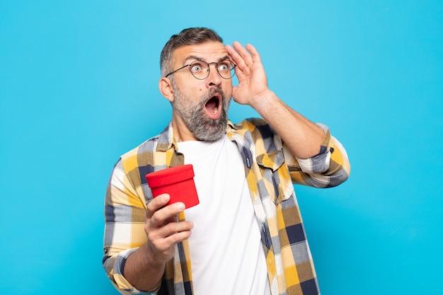 Homem adulto feliz, animado e surpreso, olhando para o lado com as duas mãos no rosto