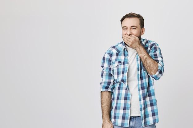 Homem adulto feliz brincalhão rindo na palma da mão, tapando a boca com a mão enquanto ri