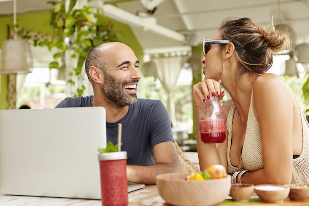 Homem adulto feliz com barba, sentado em frente ao laptop aberto, rindo alegremente, ouvindo a história da namorada, que está bebendo suco de frutas.
