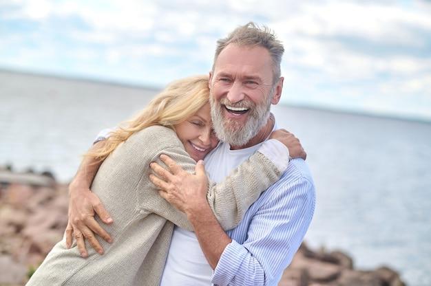 Homem adulto feliz e mulher se abraçando