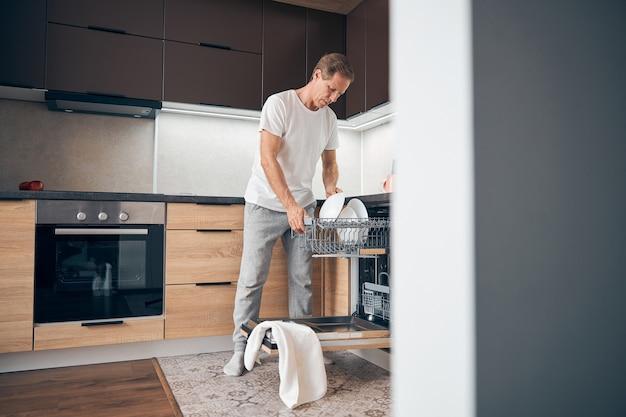 Homem adulto feliz na cozinha e limpando tudo depois do jantar