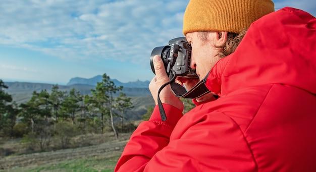 Homem adulto fotografa natureza