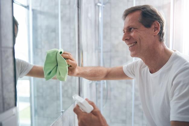 Homem adulto gentil em pé e olhando para seu reflexo enquanto limpa o espelho de seu apartamento