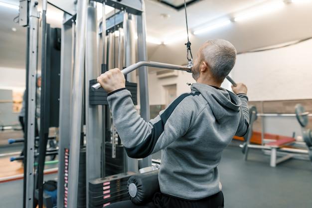 Homem adulto idade trabalhando no ginásio de treinamento