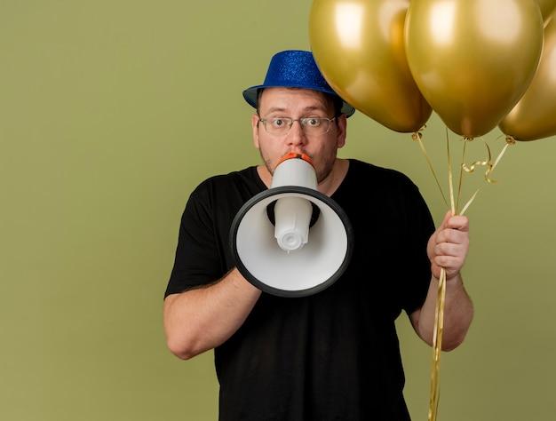 Homem adulto impressionado com óculos óticos e chapéu de festa azul segurando balões de hélio e falando no alto-falante isolado na parede verde oliva