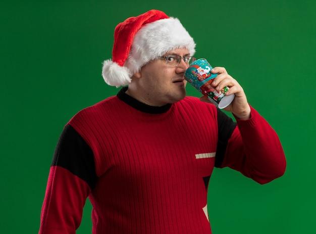Homem adulto impressionado de óculos e chapéu de papai noel bebendo café da xícara de café de natal olhando para a câmera isolada sobre fundo verde