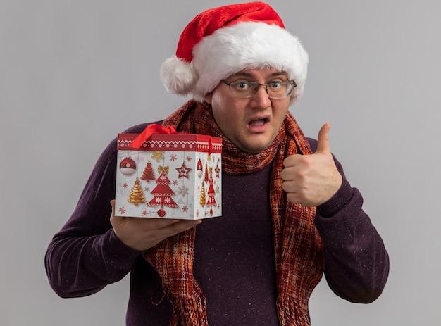 Homem adulto impressionado usando óculos e chapéu de papai noel com lenço em volta do pescoço segurando um pacote de presente de natal e mostrando o polegar isolado na parede branca