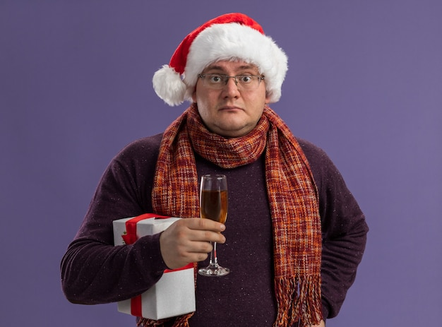 Homem adulto impressionado usando óculos e chapéu de papai noel com lenço em volta do pescoço segurando uma taça de champanhe e um pacote de presente mantendo a mão na cintura isolada na parede roxa