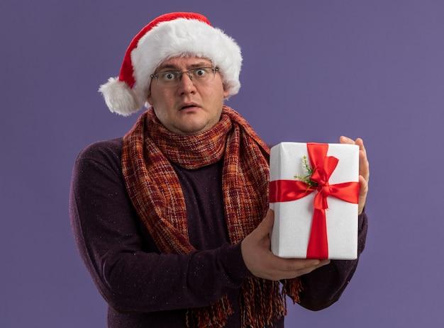 Homem adulto impressionado usando óculos e chapéu de papai noel com lenço no pescoço segurando um pacote de presente isolado na parede roxa