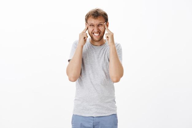 Homem adulto intenso e intrigado com cerdas nos óculos, cerrando os dentes, apertando os olhos e esticando as pálpebras para ver claramente, tendo problemas de visão ao experimentar novos óculos em loja de ótica sobre parede branca