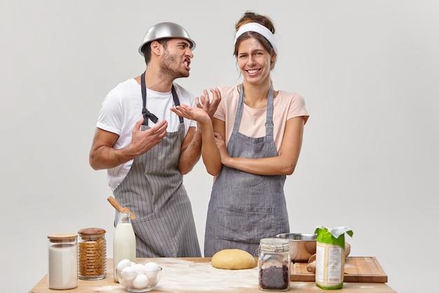 Homem adulto irritado olha para a esposa com raiva, pede para parar de cozinhar, sente-se cansado de fazer massa, mulher alegre de avental gosta de passatempo e fazer doces deliciosos. culinária e panificação durante a quarentena
