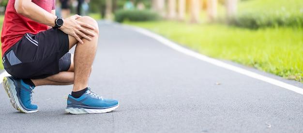 Homem adulto jovem com dores musculares durante a corrida.