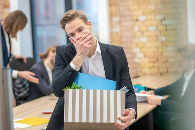 Homem adulto jovem e pensativo infeliz em um terno tocando o rosto com uma mão segurando uma caixa com coisas no escritório