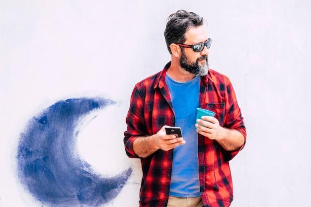 Homem adulto jovem hippie com telefone celular e camisa colorida usando um aparelho celular olhando para o lado