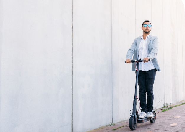 Homem adulto latino com óculos de sol, bem vestida e scooter elétrica na rua com um fundo cego branco