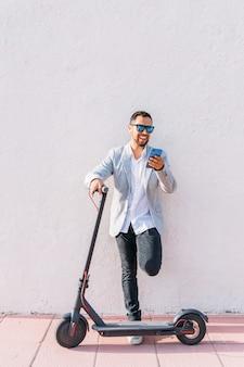 Homem adulto latino com óculos de sol, scooter elétrico bem vestido e elétrico, falando em seu telefone móvel, sentado na rua com um fundo de parede branca