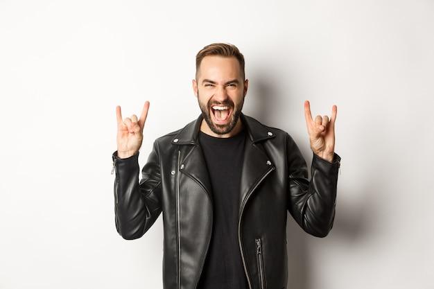 Homem adulto legal na jaqueta de couro preta, mostrando rock no gesto e na língua, curtindo o festival de música, em pé sobre um fundo branco.