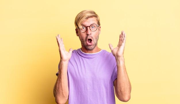 Homem adulto loiro bonito parecendo chocado e surpreso, com o queixo caído de surpresa ao perceber algo inacreditável