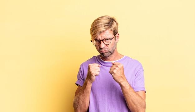 Homem adulto loiro bonito parecendo confiante, zangado, forte e agressivo, com punhos prontos para lutar em posição de boxe