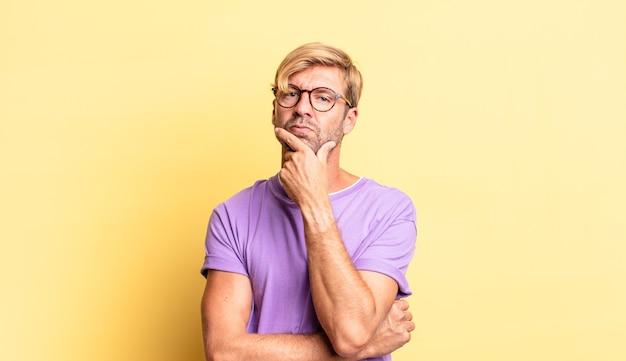Homem adulto loiro bonito parecendo sério, pensativo e desconfiado, com um braço cruzado e a mão no queixo, opções de ponderação