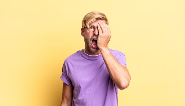 Homem adulto loiro bonito parecendo sonolento, entediado e bocejando, com dor de cabeça e uma das mãos cobrindo metade do rosto