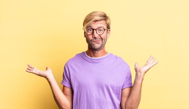 Homem adulto loiro bonito se sentindo perplexo e confuso, duvidando, ponderando ou escolhendo opções diferentes com expressão engraçada
