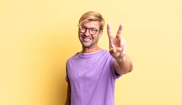 Homem adulto loiro bonito sorrindo e parecendo feliz, despreocupado e positivo, gesticulando vitória ou paz com uma mão