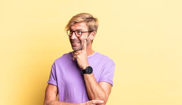 Homem adulto loiro bonito sorrindo feliz e sonhando acordado ou duvidando, olhando para o lado