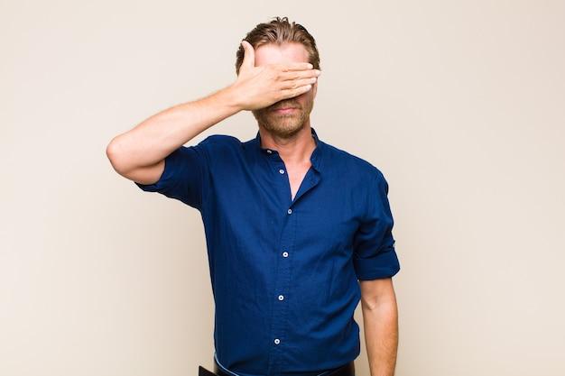 Homem adulto loiro branco cobrindo os olhos com uma mão, sentindo-se assustado ou ansioso, pensando ou esperando cegamente por uma surpresa
