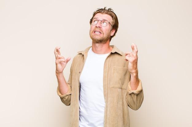 Homem adulto loiro branco cruzando os dedos ansiosamente e esperando boa sorte com um olhar preocupado
