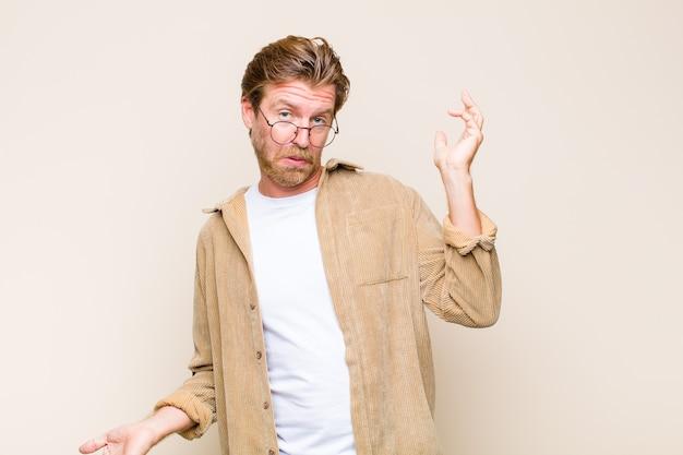 Homem adulto loiro branco encolhendo os ombros com uma expressão idiota, maluca, confusa e perplexa, sentindo-se irritado e sem noção