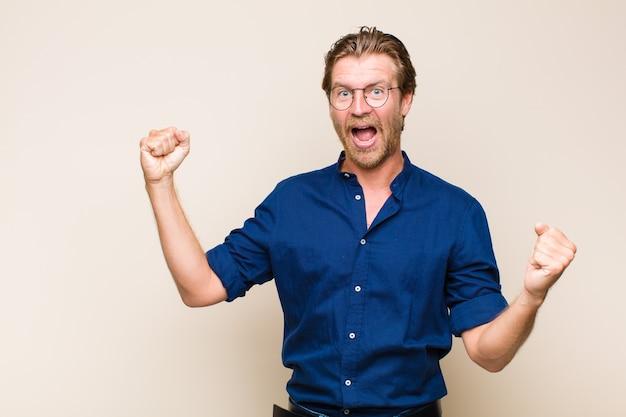 Homem adulto loiro branco gritando triunfantemente, parecendo um vencedor animado, feliz e surpreso, comemorando
