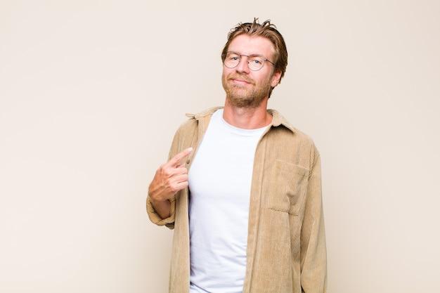 Homem adulto loiro branco parecendo orgulhoso, confiante e feliz, sorrindo e apontando para si mesmo ou fazendo o sinal de número um