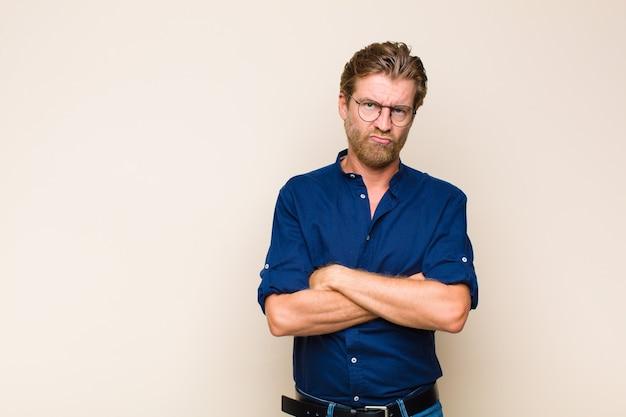 Homem adulto loiro branco se sentindo descontente e desapontado, parecendo sério, irritado e com raiva de braços cruzados