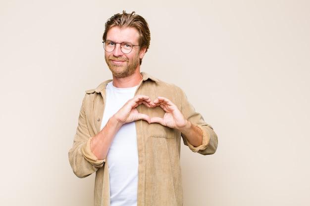 Homem adulto loiro branco sorrindo e se sentindo feliz, fofo, romântico e apaixonado, fazendo formato de coração com as duas mãos