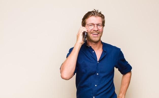 Homem adulto loiro com um celular inteligente