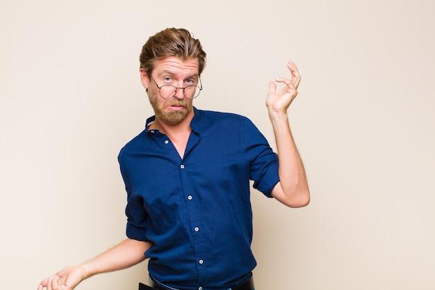 Homem adulto loiro encolhendo os ombros com uma expressão estúpida, maluca, confusa e perplexa, sentindo-se irritado e sem noção