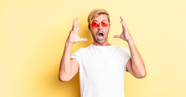 Homem adulto loiro gritando com as mãos para cima e usando óculos escuros