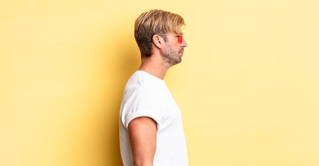 Homem adulto loiro na vista de perfil pensando, imaginando ou sonhando acordado e usando óculos escuros