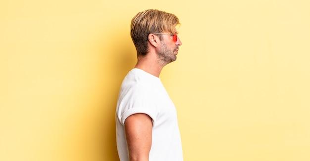 Homem adulto loiro na vista de perfil, pensando, imaginando ou sonhando acordado e usando óculos escuros