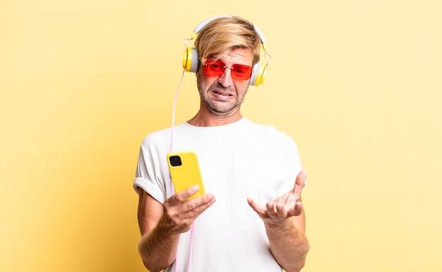 Homem adulto loiro parecendo desesperado, frustrado e estressado com fones de ouvido