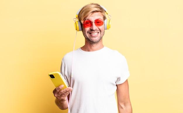 Homem adulto loiro parecendo feliz e agradavelmente surpreso com fones de ouvido