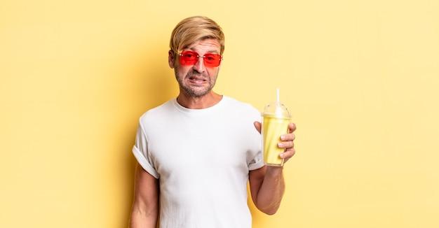Homem adulto loiro parecendo perplexo e confuso com um milkshake