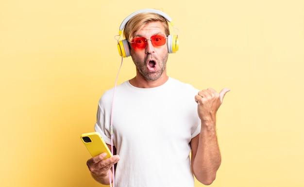 Homem adulto loiro parecendo surpreso e descrente com fones de ouvido