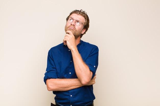 Homem adulto loiro pensando, se sentindo duvidoso e confuso, com diferentes opções, imaginando qual decisão tomar